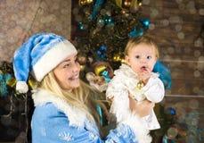 Niña y madre en el día de fiesta de la Navidad Fotos de archivo