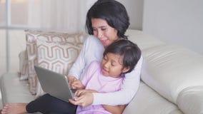 Niña y madre felices que usa el ordenador portátil almacen de video