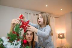 Niña y madre que colocan la estrella roja en el top de la Navidad Imágenes de archivo libres de regalías