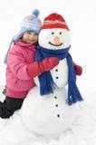 Niña y muñeco de nieve Fotos de archivo