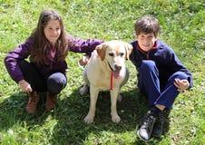 Niña y muchacho con el perro de Labrador Fotos de archivo