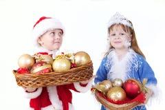 Niña y muchacho en ropa de la Navidad con los juguetes Imagen de archivo
