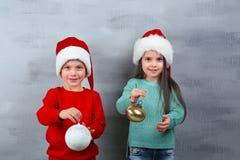 Niña y muchacho lindos en los sombreros de Papá Noel con las bolas de la Navidad Fotografía de archivo libre de regalías