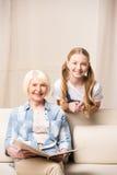 Niña y mujer mayor con el álbum de foto que sonríen en la cámara Imagen de archivo