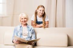 Niña y mujer mayor con el álbum de foto que sonríen en la cámara Imagen de archivo libre de regalías