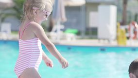Niña y papá en la piscina almacen de metraje de vídeo