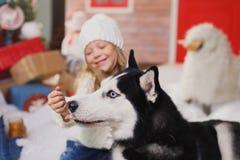 Niña y perro felices en la Navidad Imagenes de archivo