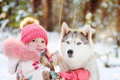 Niña y perro hasky junto en parque del invierno Foto de archivo