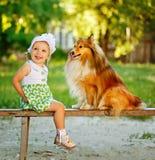 Niña y perro que se sientan en un banco Foto de archivo