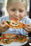Niña y pizza Imagenes de archivo