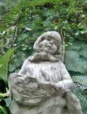 Niña y sostener la escultura de la cesta de fruta y la vid verde en jardín inglés Imagen de archivo