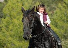 Niña y su caballo negro Imagenes de archivo