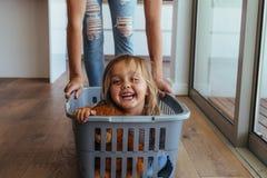 Niña y su madre que se divierten que hace el lavadero imagenes de archivo
