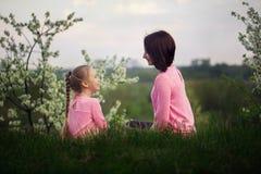 Niña y su madre que se sientan en hierba en día de verano Visión desde una parte posterior foto de archivo libre de regalías