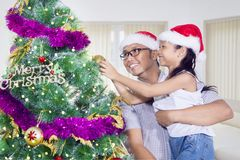 Niña y su padre que adornan el árbol de navidad Foto de archivo libre de regalías
