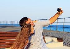 Niña y su papá que se divierten cierto en la playa y que toman un selfie Foto de archivo