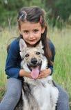 Niña y su perro del lobo del bebé Imagenes de archivo