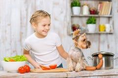 Niña y su perro en la tabla de cocina fotografía de archivo libre de regalías