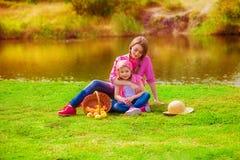 Niña y una más vieja hermana cerca de un río en el otoño Fotos de archivo