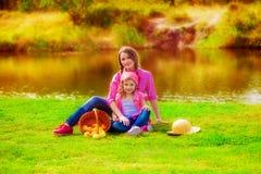 Niña y una más vieja hermana cerca de un río en el otoño Fotografía de archivo libre de regalías