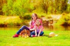Niña y una más vieja hermana cerca de un río en el otoño Fotos de archivo libres de regalías