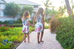 Niñas adorables en centro turístico exótico en la puesta del sol Imágenes de archivo libres de regalías