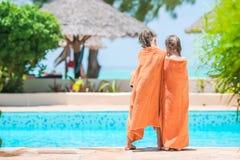 Niñas adorables envueltas en toalla al borde de piscina Imágenes de archivo libres de regalías