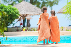 Niñas adorables envueltas en toalla al borde de piscina Imagen de archivo