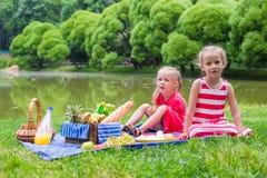 Niñas adorables picnicing en el parque en foto de archivo libre de regalías