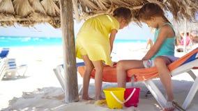 Niñas adorables que juegan con los juguetes el vacaciones de la playa Juego de los niños con los juguetes de la arena y de la pla metrajes