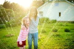 Niñas adorables que juegan con una regadera en un patio trasero en día de verano soleado Niños lindos que se divierten con agua a imagenes de archivo