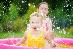 Niñas adorables que juegan en piscina inflable del bebé Los niños felices que salpican en jardín colorido juegan el centro en día imagenes de archivo