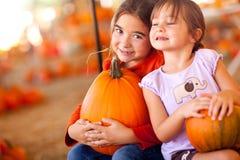 Niñas adorables que sostienen sus calabazas en un remiendo de la calabaza Imagen de archivo libre de regalías