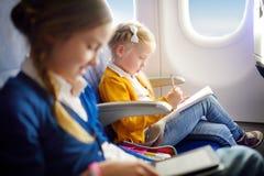 Niñas adorables que viajan por un aeroplano Niño que se sienta por la ventana de los aviones y que dibuja una imagen con los lápi Imagen de archivo