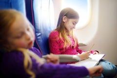 Niñas adorables que viajan por un aeroplano Niño que se sienta por la ventana de los aviones y que dibuja una imagen con los lápi Imágenes de archivo libres de regalías