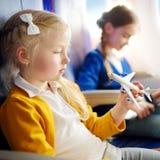 Niñas adorables que viajan por un aeroplano Niños que se sientan por la ventana de los aviones y que juegan con el avión del jugu Fotos de archivo libres de regalías