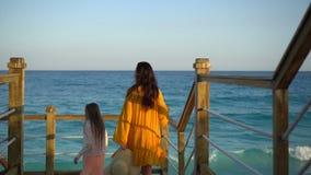 Niñas adorables y madre joven que caminan en la playa blanca por la tarde metrajes