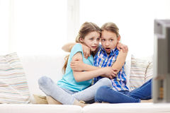 Niñas asustadas que miran horror en la TV en casa Foto de archivo