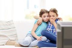 Niñas asustadas que miran horror en la TV en casa Foto de archivo libre de regalías