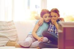 Niñas asustadas que miran horror en la TV en casa Fotos de archivo