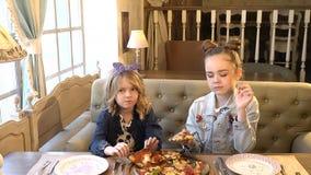 Niñas bonitas que comen hacia fuera las muchachas comen la pizza en la sonrisa del restaurante de la pizza enjoying HD lleno almacen de video