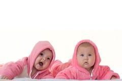Niñas en guardapolvos rosados un blanco aislado Fotografía de archivo libre de regalías