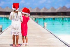 Niñas en los sombreros de Papá Noel durante vacaciones de verano Imagen de archivo libre de regalías