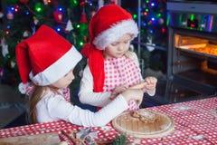 Niñas en los sombreros de Papá Noel que cuecen la Navidad Imagen de archivo