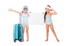 niñas en los sombreros de santa que sostienen la bandera en blanco mientras que se coloca con la maleta fotos de archivo