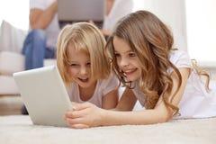 Niñas felices con el ordenador de la PC de la tableta en casa Imagen de archivo