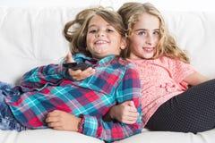 Niñas felices puestas en el sofá Fotos de archivo libres de regalías