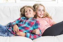 Niñas felices puestas en el sofá Imagenes de archivo