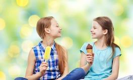 Niñas felices que comen el helado sobre verde Foto de archivo libre de regalías