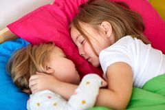 Niñas felices que duermen en cama en casa Imagen de archivo